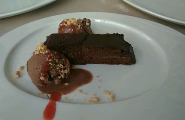 Tarta de chocolate rellena de mermelada y con cubertura de chocolate. Acompañada de una bola de helado.